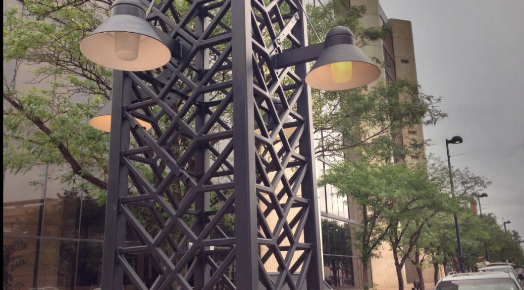 Three of four bench lights are switched on near noontime, as well as street lights for two blocks.